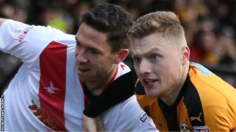 Ben Tozer of Newport County and Cambridge United's George Maris tussle as they chase the ball
