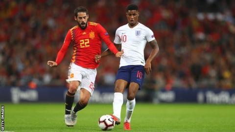 England goalscorer Marcus Rashford competes with Isco