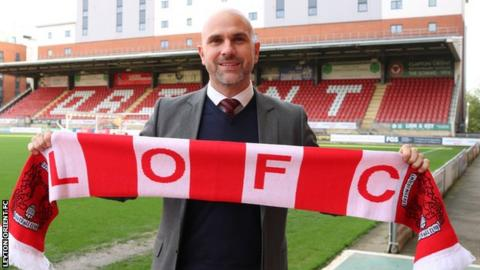 New Leyton Orient head coach Carl Fletcher holds up a club scarf