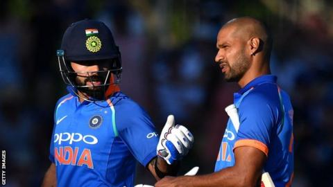 India captain Virat Kohli and opener Shikhar Dhawan walk off the field in Napier after the sun halted play against New Zealand
