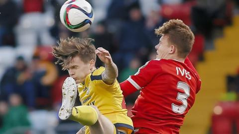 Dungannon Swifts striker Paul McElroy feels the full force of this collision with Cliftonville defender Levi Ives at Solitude