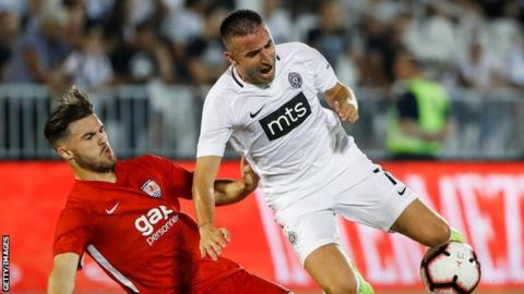 Zoran Tosic (R) of Partizan is challenged by Callum Roberts of (L) Connah's Quay