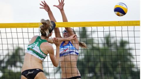 SINGAPORE - JUNE 22: Megan McNamara of Canada (R) attempts to block Phoebe Bell of Australia spikes during the main draw pool C women's match on day one of the FIVB Beach Volleyball World Tour Singapore at Siloso Beach on June 22, 2018 in Singapore. (Photo by Suhaimi Abdullah/Getty Images)