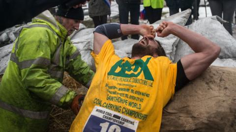 A competitor collapses at the finish line of a race at the annual World Coal Carrying Championships in the village of Gawthorpe, near Wakefield, northern England on April 2, 2018