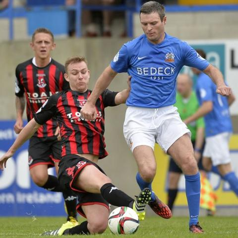 Andy Mitchell of Crusaders attempts to get to the ball before Glenavon opponent Kevin Braniff at Mourneview Park