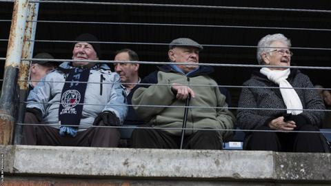 A group of elderly fans in the main stand await the arrival of the teams on to the pitch prior to the kick-off