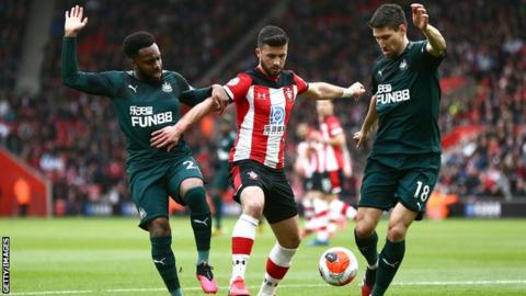 Shane Long of Southampton is challenged by Danny Rose and Federico Fernandez of Newcastle United
