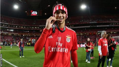 Joao Felix bites his league winner's medal after winning the title with Benfica
