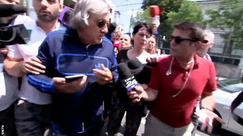 Ilie Nastase surrounded by reporters as he left the police station in Bucharest