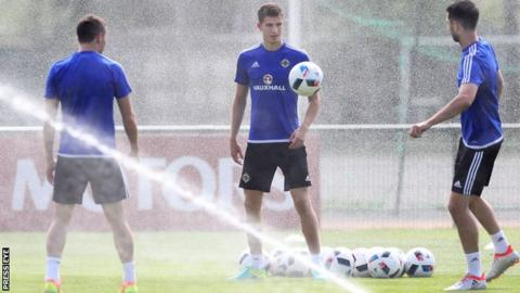 Paddy McNair manages to avoid the sprinklers during Monday morning's training session in Saint-Georges-de-Reneins