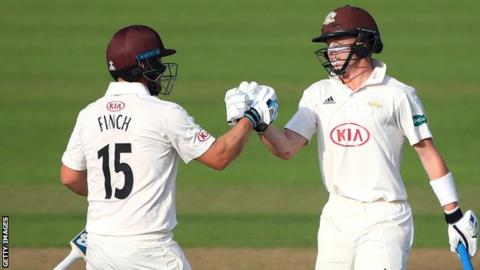 Surrey batsmen Aaron Finch and Ollie Pope celebrate a landmark in their innings against Hampshire
