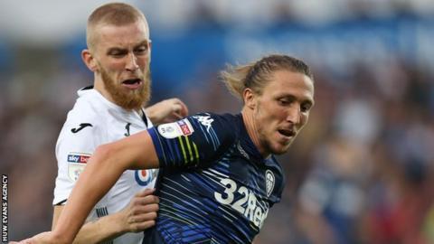 Oli McBurnie and Leeds United's Luke Ayling tussle for possession