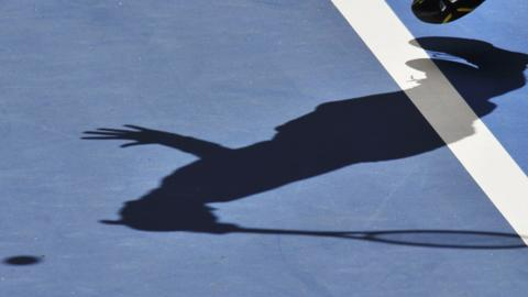Tennis player in shadow
