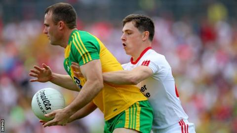 Donegal's Neil McGee shields the ball from Niall Sludden of Tyrone