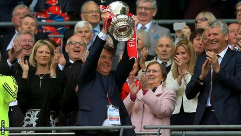Man Utd manager Louis van Gaal lifts the FA Cup trophy as former Red Devils boss Sir Alex Ferguson looks on