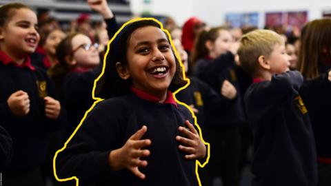 Children moving to a Brain Booster video in a school hall.
