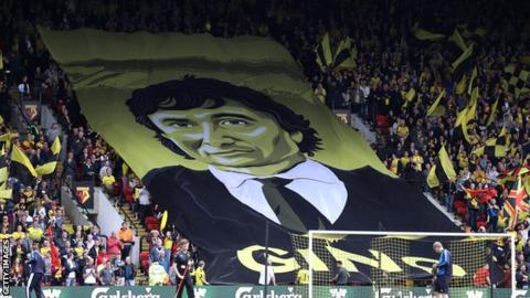 Watford fans fly a flag with the face of owner Gino Pozzo