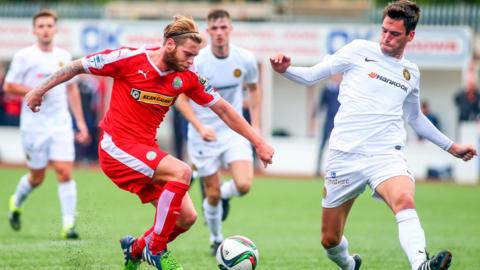 Cliftonville's James Knowles and Mark Surgenor of Carrick Rangers in action at Solitude