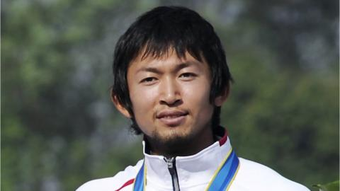 "Joint bronze medalist Yasuhiro Suzuki of Japan attends the medal ceremony for the men""s kayak single 1000m final at the International Rowing Centre in Guangzhou during the 16th Asian Games"