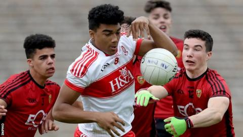 Derry forward Callum Brown attempts to move clear of Down pair Finn McIlroy and Daniel Guinness