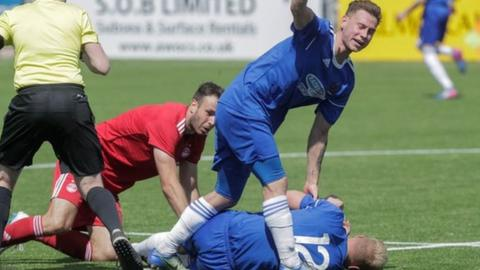 Jordon Brown (grounded) lies prone after a collision with Aberdeen's Andrew Considine