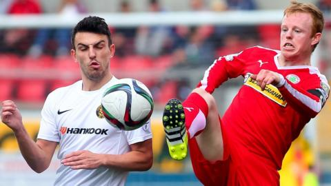 Conor McCloskey of Carrick Rangers in action against George McMullan who scored the goal in Cliftonville's 1-0 home victory