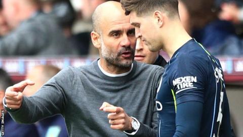Manchester City boss Pep Guardiola with John Stones