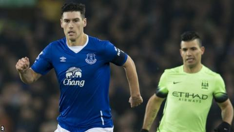 Everton midfielder Garerth Barry is pursued by Manchester City striker Sergio Aguero
