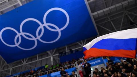 A Russian flag is waved in front of the Olympic rings at Pyeongchang 2018