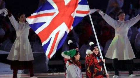 Britain's Menna Fitzpatrick carries the flag at the closing ceremony
