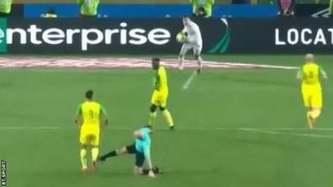 Referee Tony Chapron aiming a kick at Diego Carlos