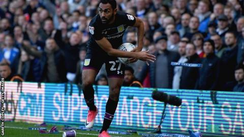 Ahmed Elmohamady of Aston Villa removes debris from the pitch during Sunday's second city derby