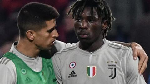 Juventus forward Moise Kean is consoled by team-mate Joao Cancelo after being racially abused during a Serie A match in Cagliari