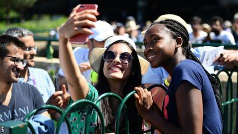 Coco Gauff poses with a fan for a picture