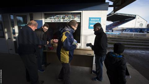 Fans buy matchday programmes