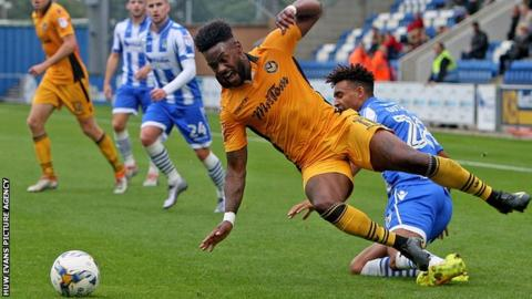 Jennison Myrie-Williams is tackled by a Colchester defender