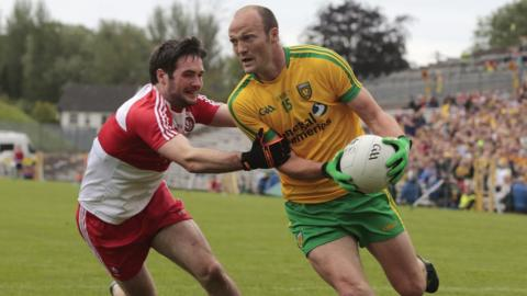 Oisin Duffy of Derry attempts to halt the progress of Donegal forward Colm McFadden