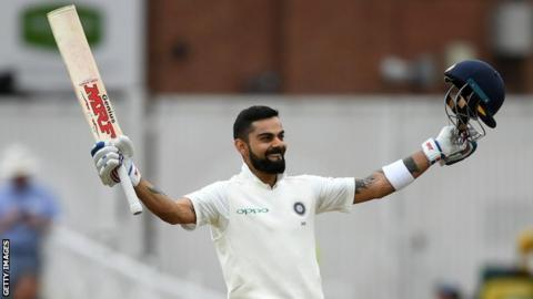 India captain Virat Kohli celebrates scoring a century by raising his bat and helmet