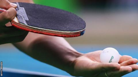 A table tennis ball and paddle