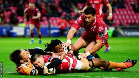 Wing Steff Evans scores a try on his 100th Scarlets appearance