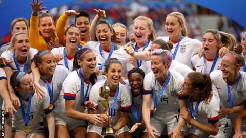 The US women's football team prepare to lift the 2019 World Cup on the podium