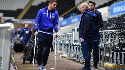 Connor Wickham of Crystal Palace walks out of the Liberty Stadium on crutches