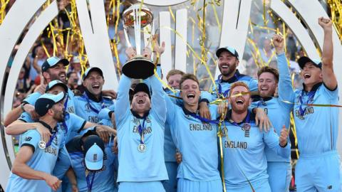 """England""""s captain Eoin Morgan lifts the World Cup trophy as England""""s players celebrate their win after the 2019 Cricket World Cup final between England and New Zealand at Lord""""s Cricket Ground in London on July 14, 2019. - England won the World Cup for the first time as they beat New Zealand in a Super Over after a nerve-shredding final ended in a tie at Lord""""s on Sunday. (Photo by Glyn KIRK / AFP)"""