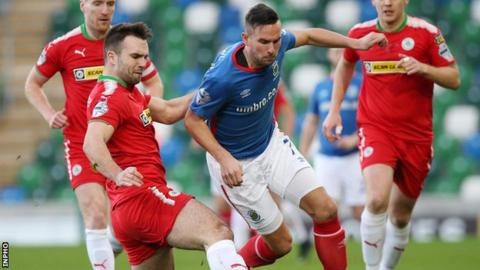 Cliftonville's Jamie Harney in action against Andrew Waterworth of Linfield