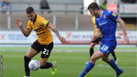 Tyler Forbes of Newport County takes on Morecambe's Rhys Oates