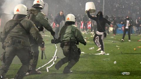 Riot police clash with PAOK fans during their Greek Cup semi-final against Olympiakos