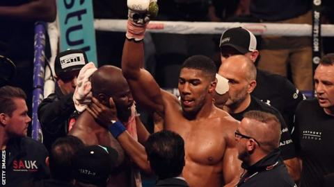 Anthony Joshua's arm is lifted in triumph after Carlos Takam is stopped in Cardiff