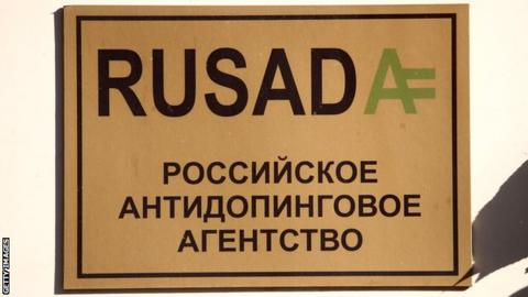 A gold sign with black lettering of the name Rusada, outside the the Russian anti-doping agency in Moscow