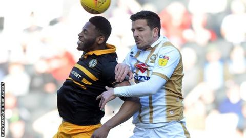Mathieu Baudry of MK Dons goes for a header with Newport's Jamille Matt