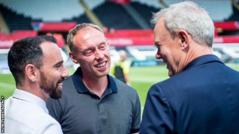 Leon Britton, Steve Cooper and Swansea City chairman Trevor Birch chat before a game